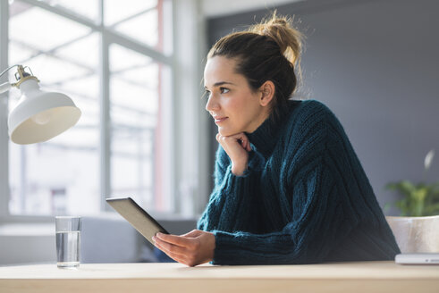 Portrait of smiling woman sitting at desk with digital tablet looking at distance - MOEF01855