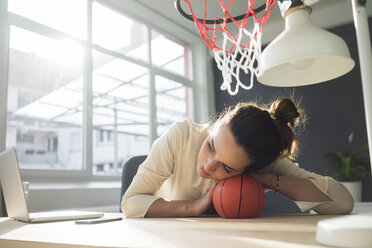 Freelancer relaxing with basketball at desk in a loft - MOEF01858