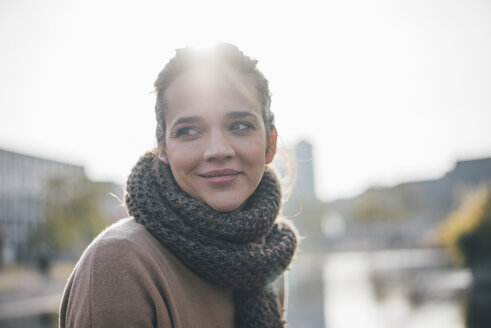 Portrait of smiling woman wearing scarf at backlight - MOEF01861