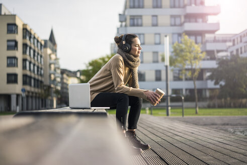 Woman with coffee to go sitting on bench in autumn listening music with laptop and cordless headphones - MOEF01864