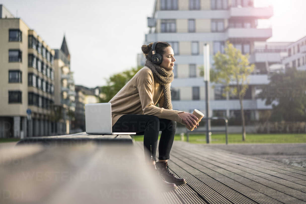 Woman with coffee to go sitting on bench in autumn listening music with laptop and cordless headphones - MOEF01864 - Robijn Page/Westend61