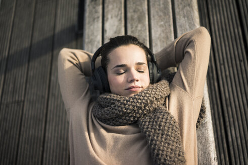 Portrait of woman listening music with cordless headphones relaxing on bench in autumn - MOEF01867