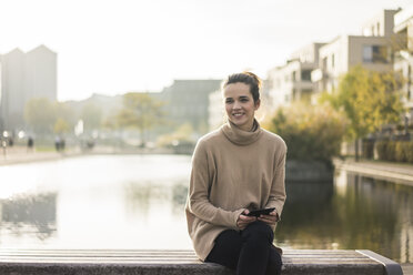 Portrait of smiling woman with digital tablet sitting on bench in autumn - MOEF01870