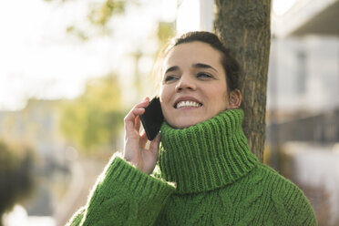 Portrait of happy woman on the phone wearing green turtleneck pullover in autumn - MOEF01873
