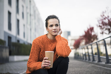 Portrait of pensive woman with coffee to go wearing orange knit pullover outdoors - MOEF01876