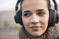 Portrait of smiling woman wearing scarf listening music with cordless headphones, close-up - MOEF01882