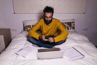 Young man working in bed at home with cell phone, laptop and documents - JRFF02146