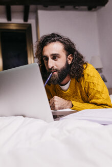 Young man lying in bed at home using laptop - JRFF02155