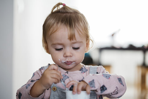 Portrait of baby girl eating yogurt at home - JRFF02181