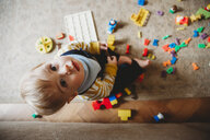 Overhead portrait of cute baby boy with toys sitting on carpet at home - CAVF57968
