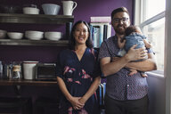Portrait of happy parents with daughter standing by window in kitchen at home - CAVF58067