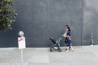 Parents with daughter in baby stroller walking on sidewalk - CAVF58070