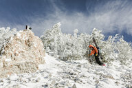 Low angle view of woman with skies hiking on snow covered mountain against sky - CAVF58082