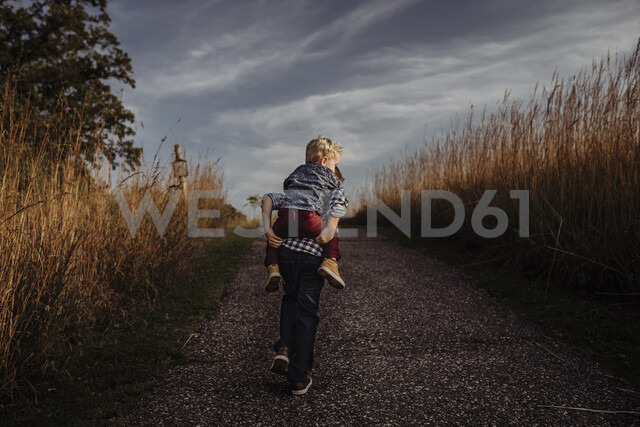 Rear view of boy piggybacking brother on country road against stormy clouds - CAVF58097