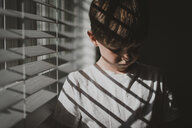 Boy standing by window at home - CAVF58184