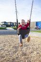 Cute baby boy swinging against sky at park - CAVF58205