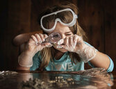 Girl looking at object through magnifying glass while sitting at table - CAVF58208