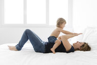 Happy mother playing with daughter while lying on bed at home - CAVF58247