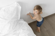 High angle portrait of shirtless baby girl standing by bed on floor at home - CAVF58253