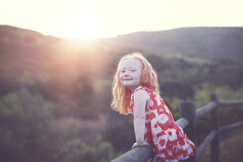 Portrait of playful girl leaning on railing against mountains during sunset - CAVF58277