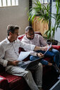 Two businessmen using laptop and discussing documents on sofa in loft office - GIOF04975
