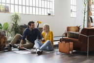 Smiling businessman and businesswoman sitting on the floor discussing documents in loft office - GIOF05005