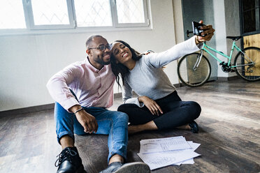 Smiling businessman and businesswoman sitting on the floor taking a selfie - GIOF05029