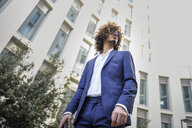 Young fashionable businessman with curly hair wearing blue suit and sunglasses - JSMF00645