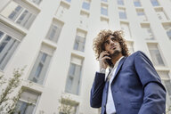 Portrait of young businessman with curly hair on the phone - JSMF00648