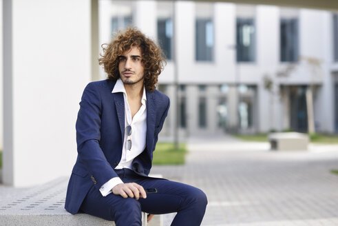 Portrait of young businessman with curly hair wearing blue suit sitting on bench outdoors - JSMF00654