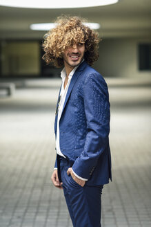 Portrait of young fashionable businessman with curly hair wearing blue suit - JSMF00666