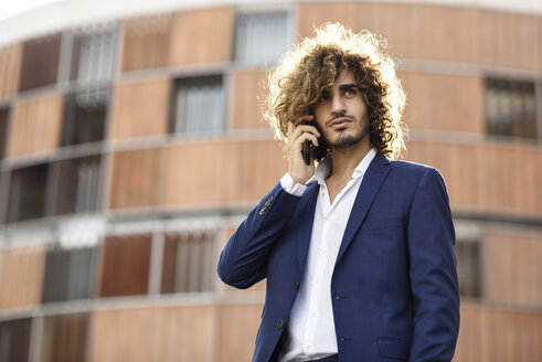 Portrait of young fashionable businessman with beard and curly hair on the phone - JSMF00669