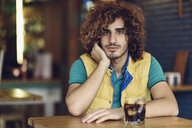 Portrait of young man with beard and curly hair drinking cola in a pub - JSMF00684