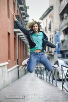 Portrait of smiling young man jumping in the air outdoors - JSMF00693