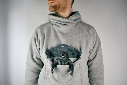 Action figure inside the front pocket of a man with sweater - INGF08721