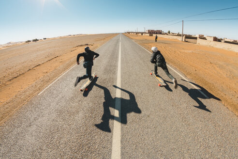 Full length rear view of friends skateboarding on road against sky during sunny day - CAVF58294