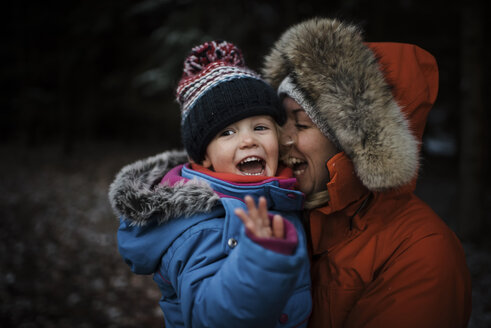 Happy mother carrying daughter while standing at forest during winter - CAVF58348