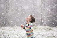 Side view of happy boy sticking out tongue while standing on field during snowfall - CAVF58360