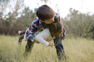 Boy carrying sister while playing on field at park - CAVF58399