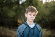 Portrait of boy standing in forest - CAVF58405