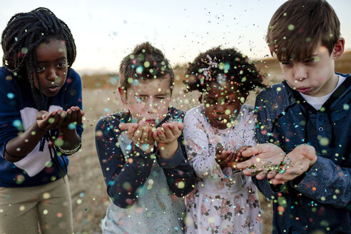 Siblings blowing confetti while standing against sky at forest - CAVF58411