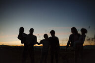 Silhouette family standing against sky at forest during sunset - CAVF58414