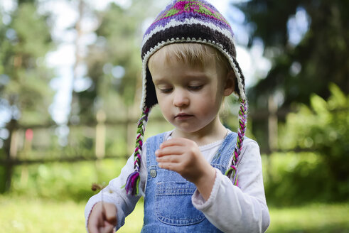 Portrait of little girl wearing knitted hat watching something in her hand - PSIF00173