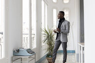 Young businessman standing in office looking out of the window - GRSF00018