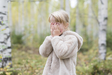 Blond girl playing Hide and Seek in a forest - PSIF00181