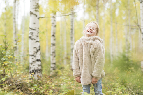 Portrait of laughing blond girl playing in autumnal forest - PSIF00184