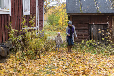 Finland, Kuopio, mother and little daughter playing together in autumn - PSIF00190