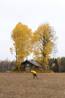 Finland, Kuopio, woman in yellow rain jacket collecting autumn leaves - PSIF00196