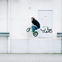 Action shot of a man riding a children's bicycle against a white wall - INGF08859