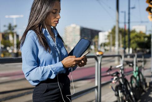 Businesswoman using smartphone, laptop bag - MAUF01825